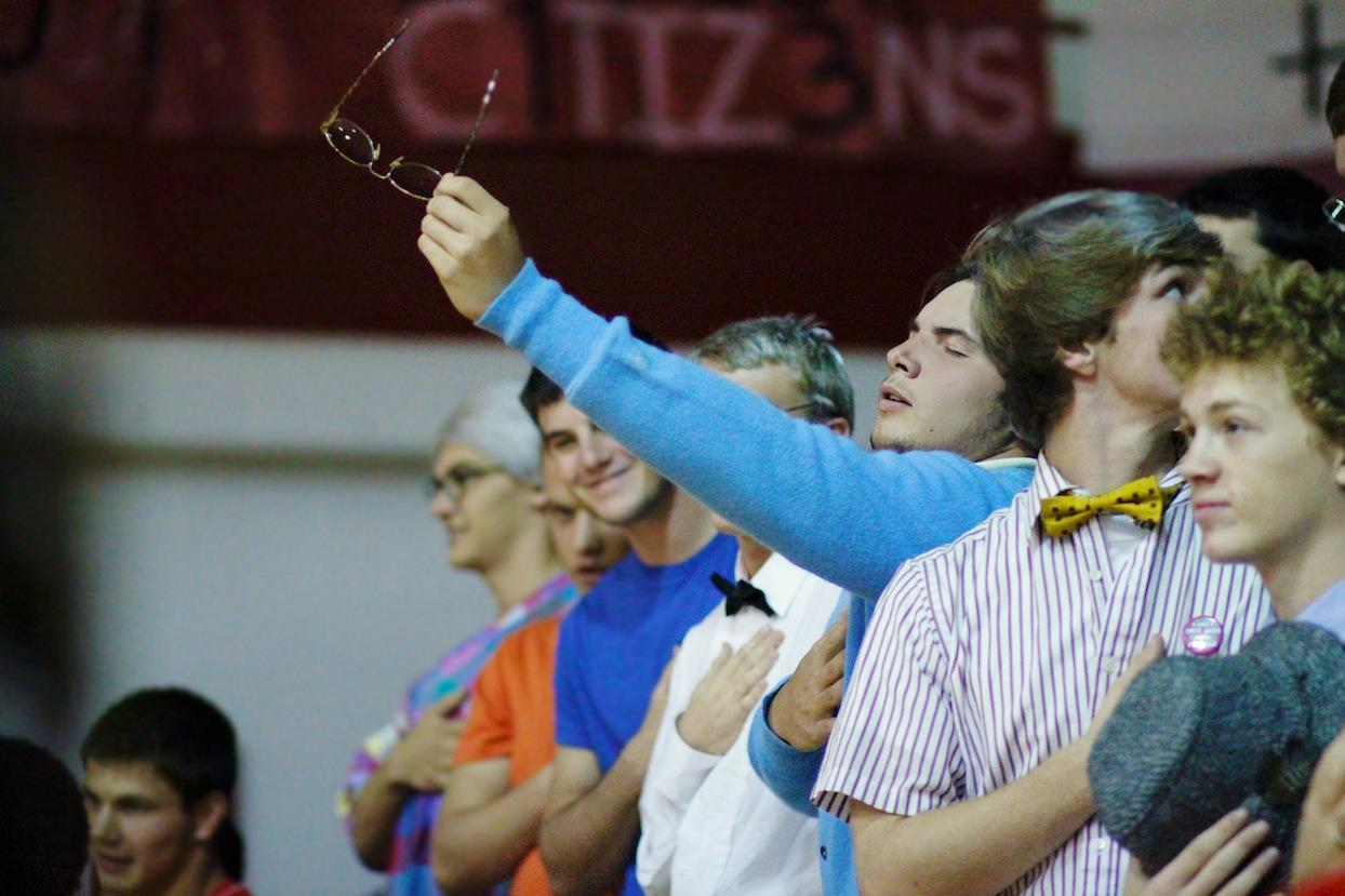 Joshua Brentlinger holds out his glasses during the National Anthem.