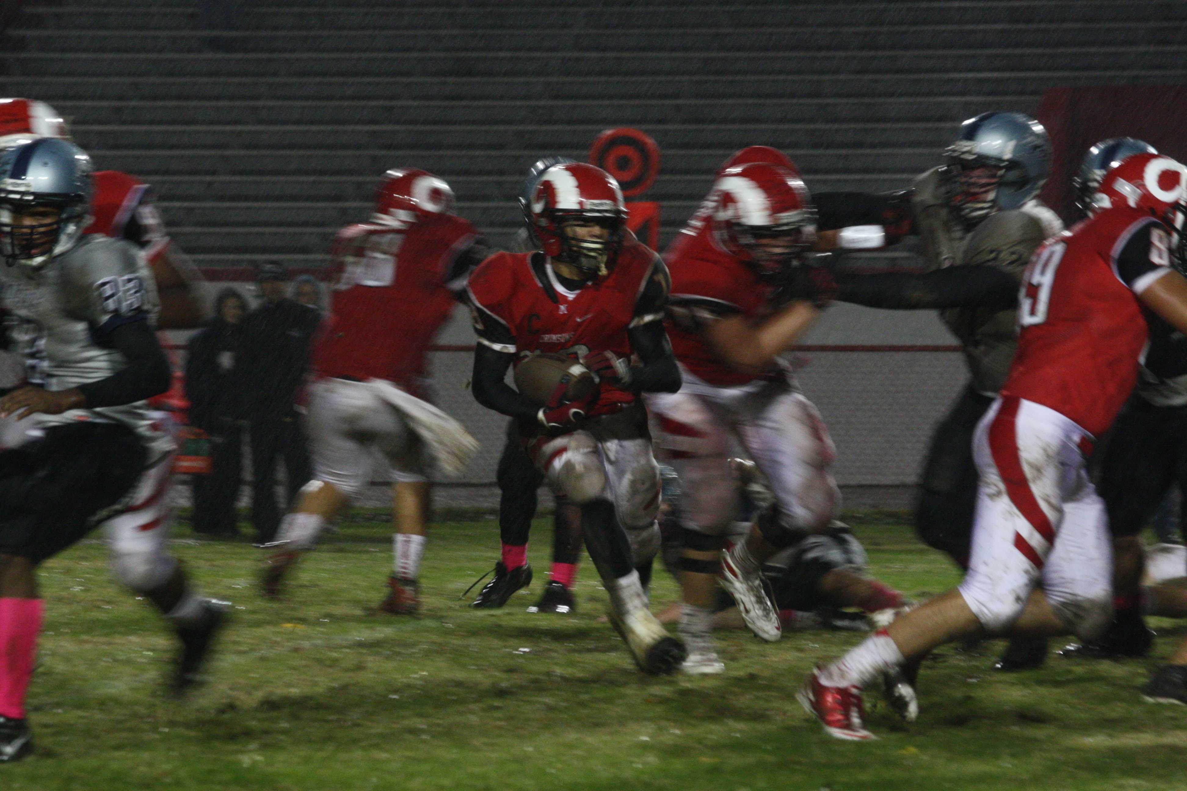 Dishan Romine (12) runs the ball as his teammates hold off the defense. photo by Destony Curry