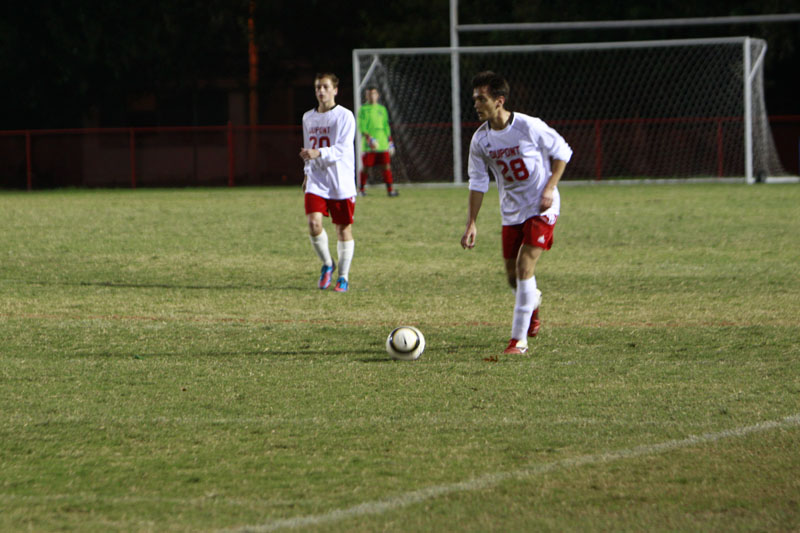 Stefan Sajic (12) dribbles the ball down the field looking towards the goal for someone to pass to.