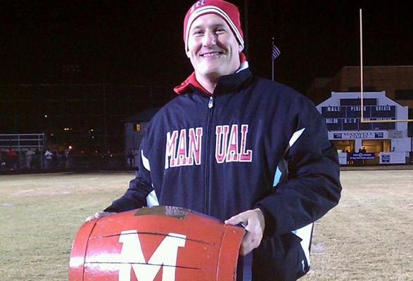 Manual's athletic director Dave Zuberer poses with the barrel after Manual's 24-14 victory over rival Male High School.