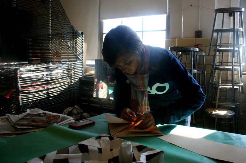 In order to make an origami themed hat, Amber Kleitz (12) looks up instructions.