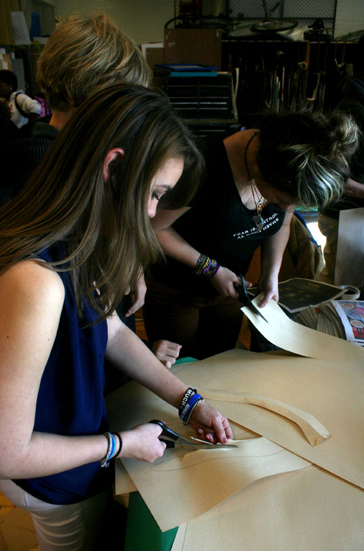 Makena Devlin (11) and Jenna Farineau (11) begin to cut strips of paper for their hats
