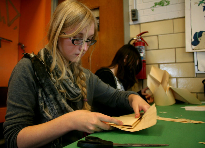 Kyleen Johnsson (10) uses a folding technique to make her hat.