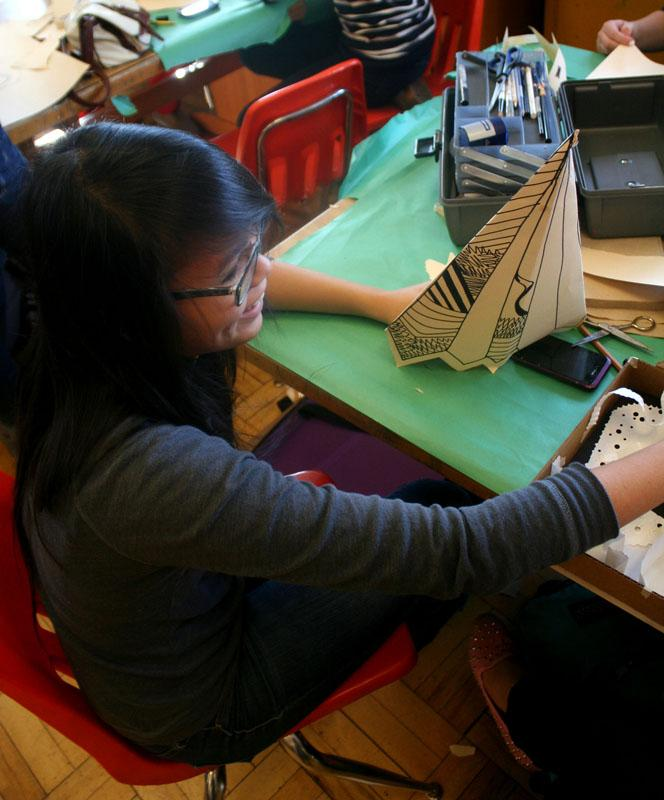 Jessica Tran (9) makes a princess style hat and uses a thin point sharpie to etch designs onto it.