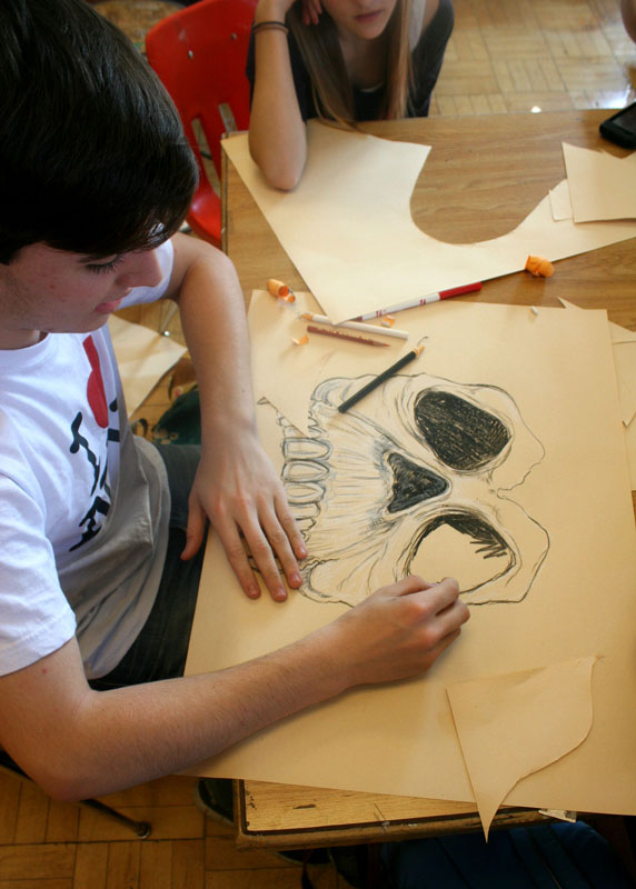 Michael Crawford (10) chooses a darker theme, and with colored pencils, begins to sketch a skull hat