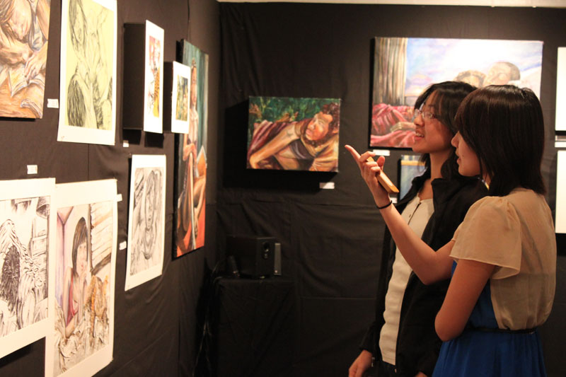 Ava Chen (12) discusses one of the paintings with a fellow on-looker.