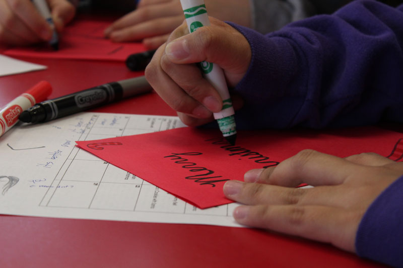 Katherine Raible (11) covers her card in holiday decorations and messages.