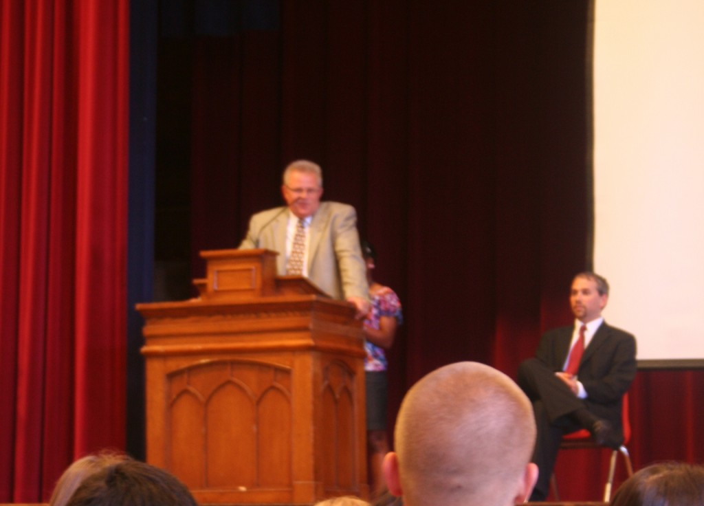 Two principal candidates answer student questions in auditorium