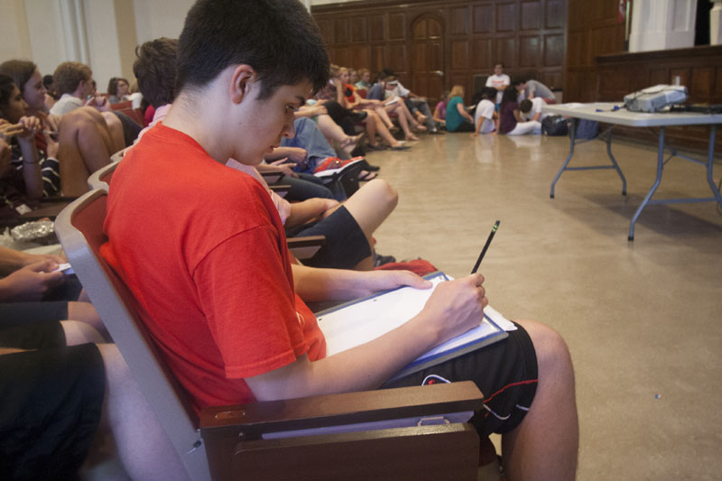 Shay Dobson (9) takes notes on the candidates. Photo by Kelsi White