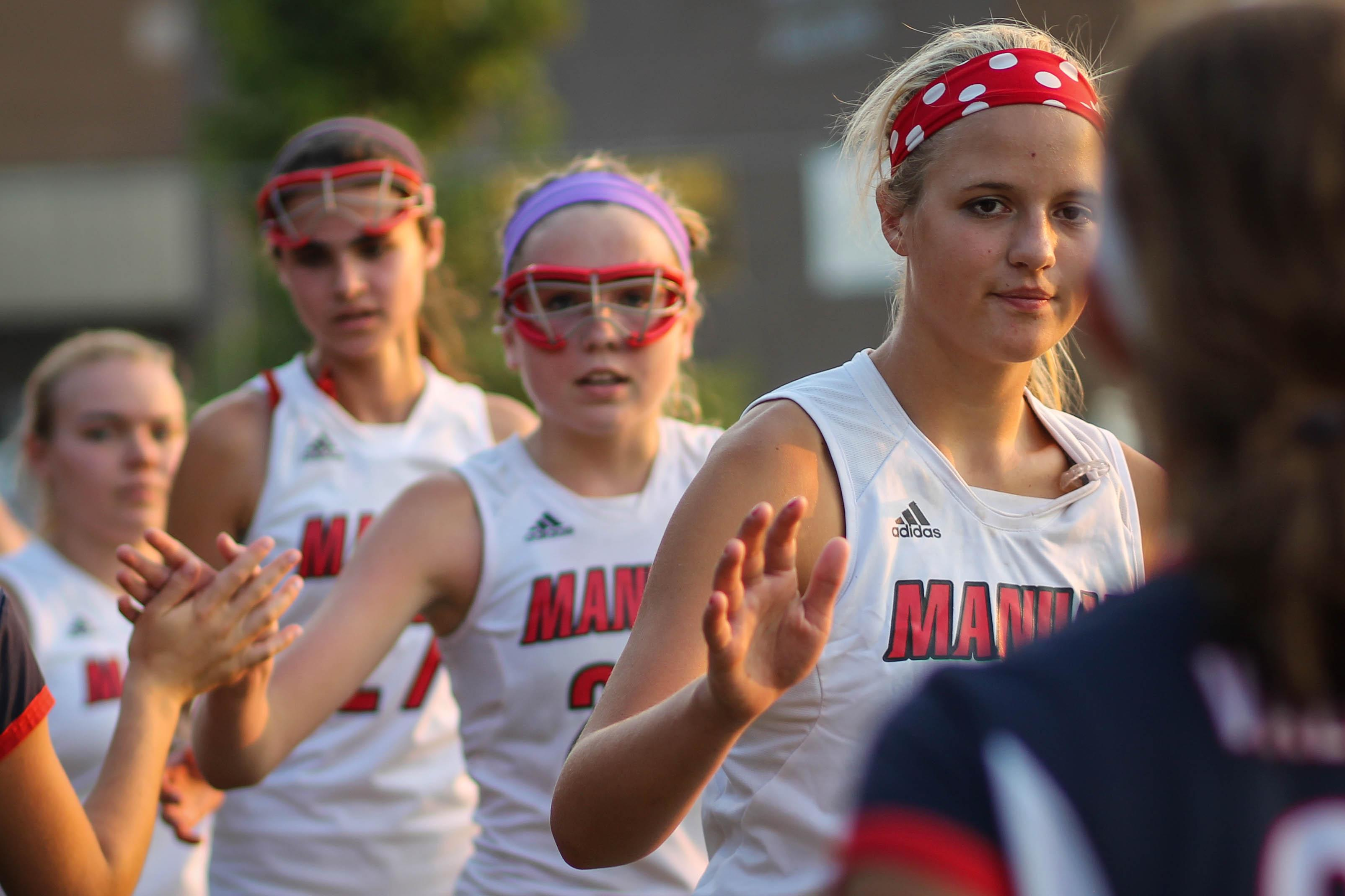 Katherine Stodgehill (11, 3rd from left) shakes hands with opponent following a game against Sacred Heart Academy.