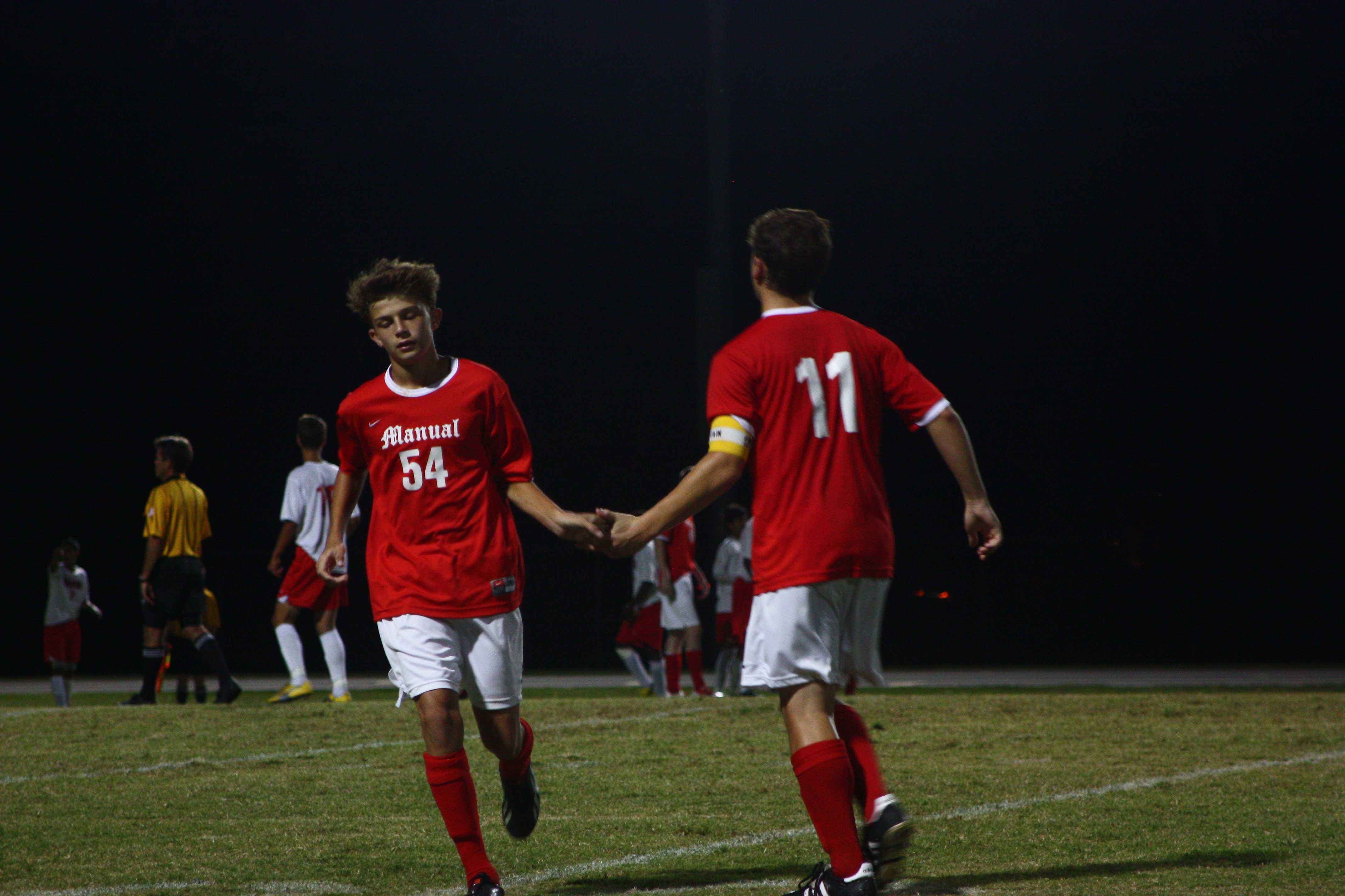 Sam Ross (12, #11) shows good sportsmanship towards his teammate Jason Kidwell (9,#54) when substituting.