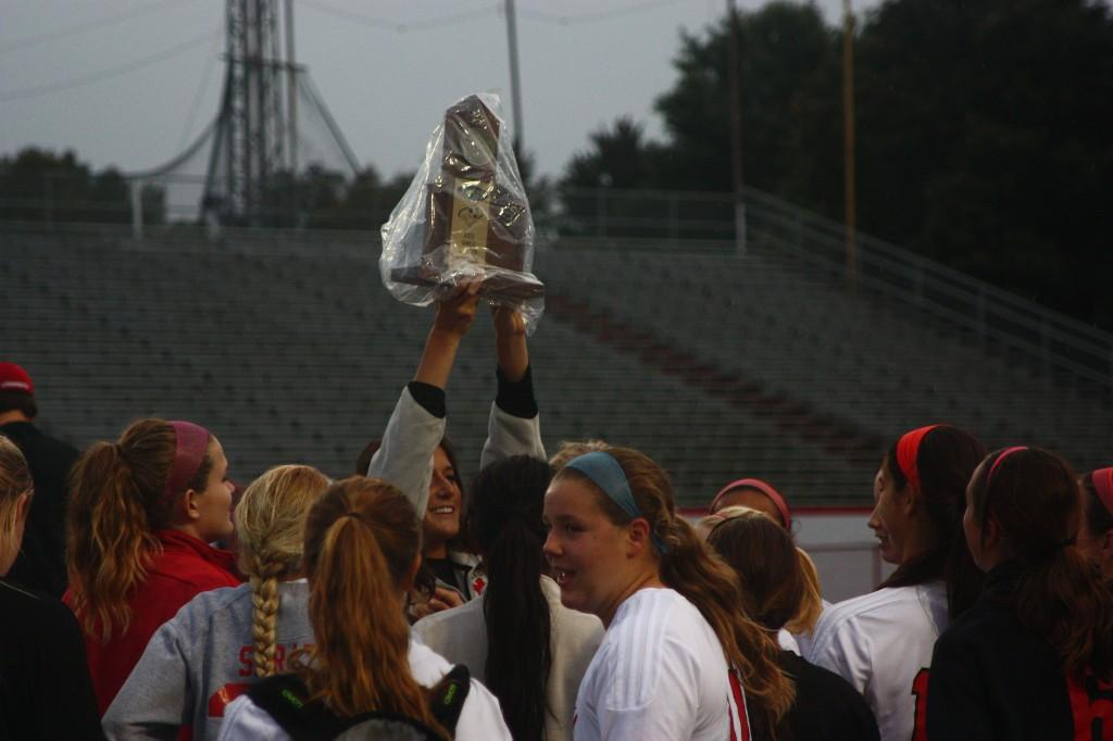 Emily Wilbar hoists the district champion trphy above her team in celebration of their victory over Presentation