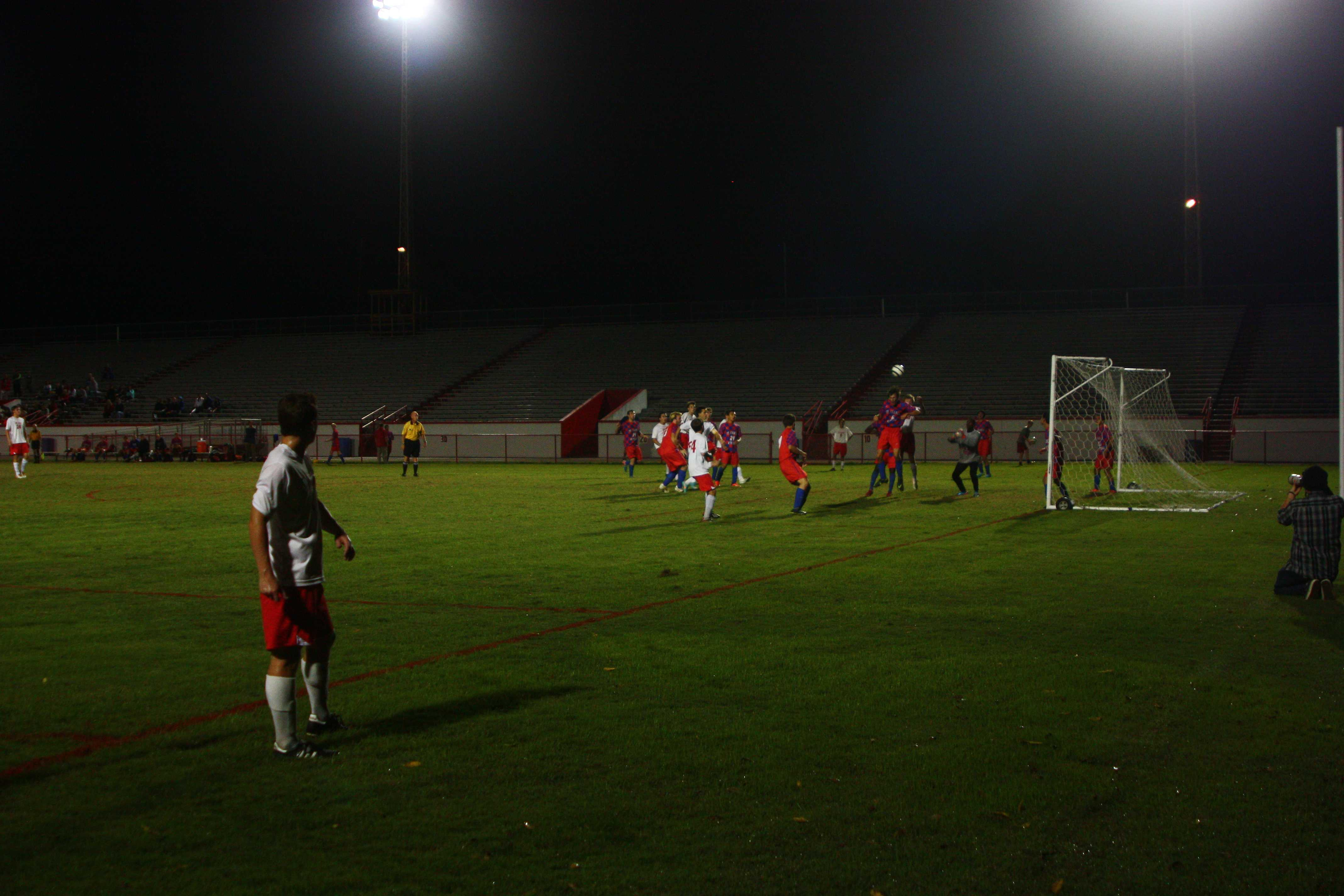 Sam Ross (12, #11) watches the play unfold after kicking a corner-kick in front of the goal