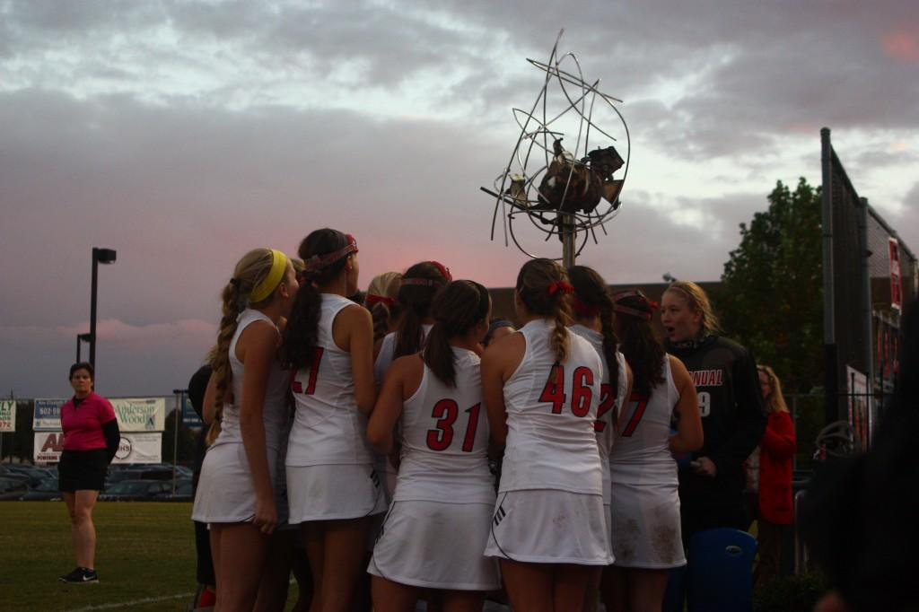 Before the game, Manual players sing the school fight song while huddled around a landmark sculpture