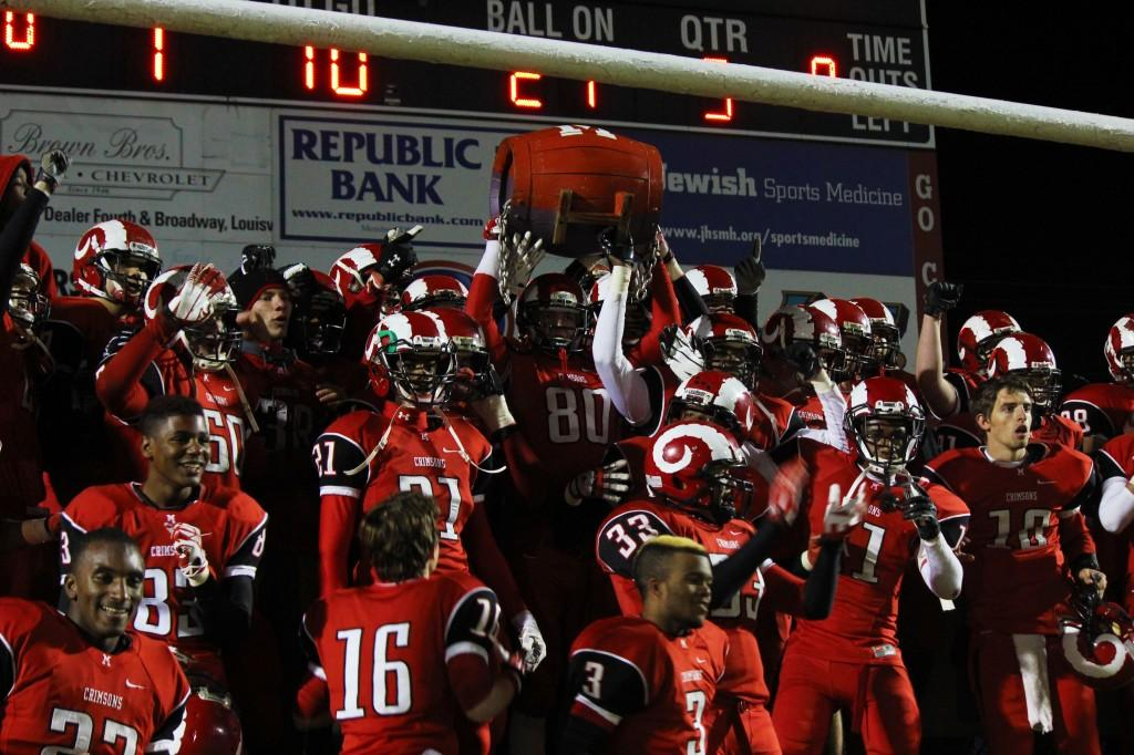 At the end of the game, the football team lines up to take a picture with the barrel right after their win.