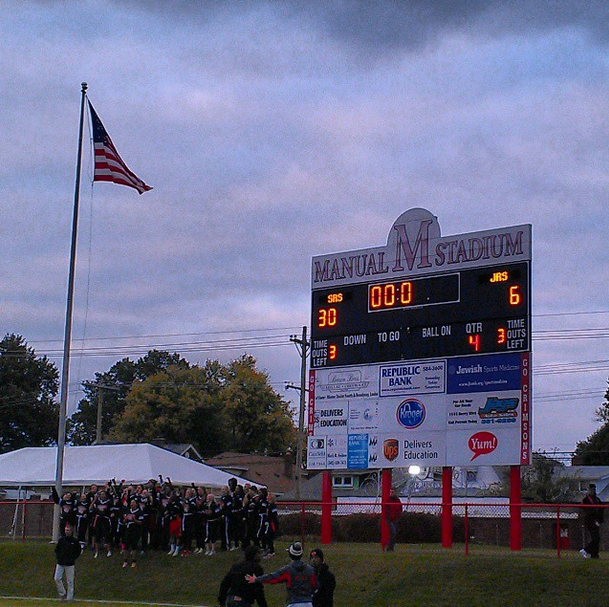 The Manual Seniors celebrate their victory beside the scoreboard, where they sang
