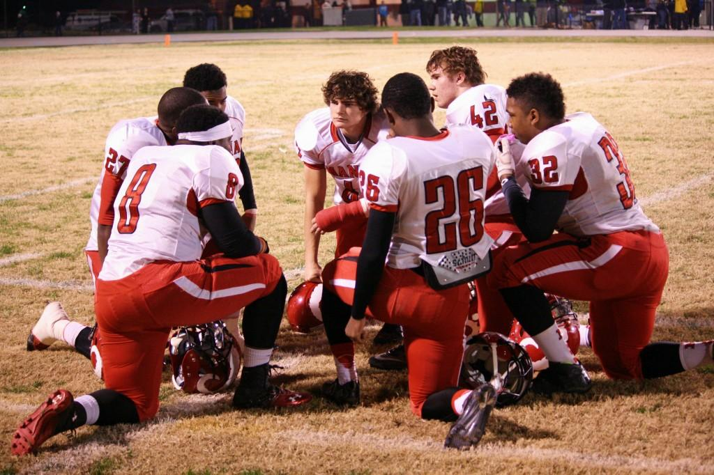 A pre-game meeting among seven of Manual's players.