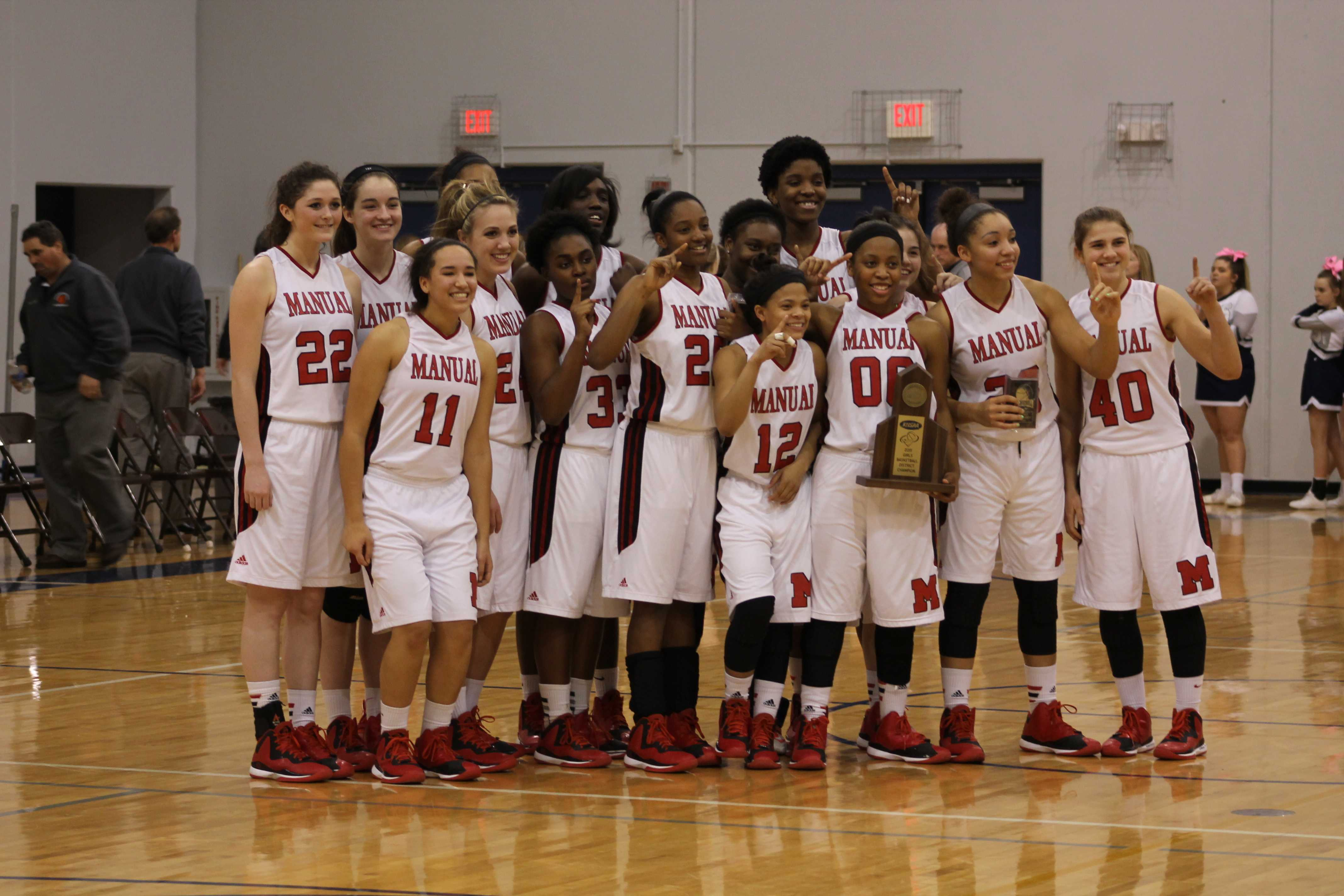 The Lady Crimsons pose with their trophy after winning the district tournament. Manual will now advance to the regional tournament.