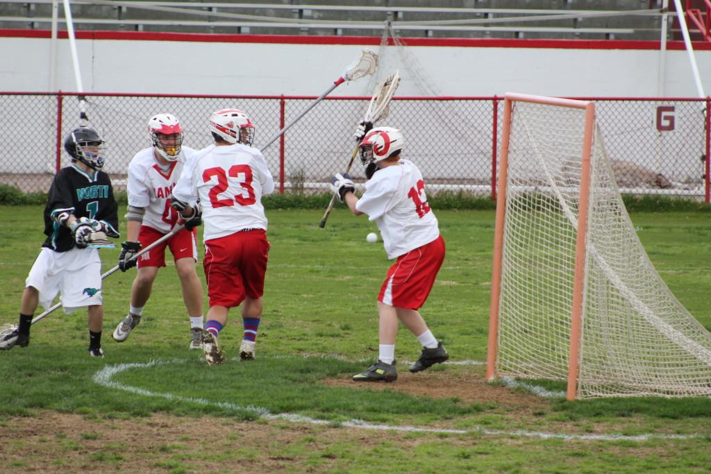 Goalie John Biggs (12, #12) prepares to block a shot on goal with his net. However, the ball instead hit Biggs in the side and missed the goal.