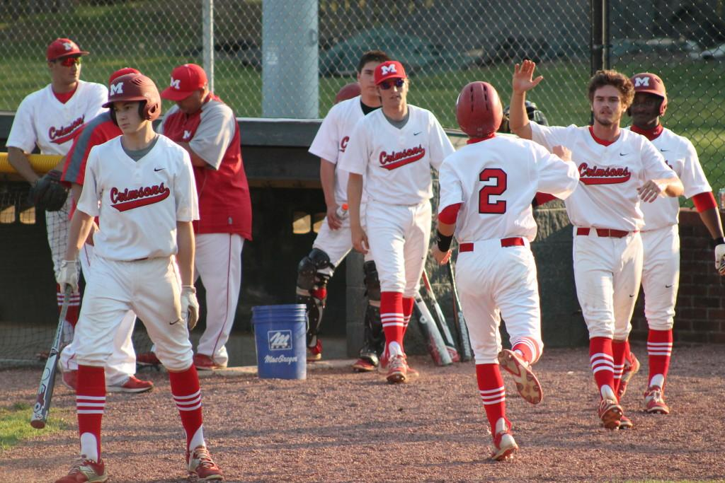 Matt Olson (11, #2) celebrates with Matthew Marino (12, #7) and others after scoring Manual's first run of the game off of a hit by Aaron Sary (9, #20).