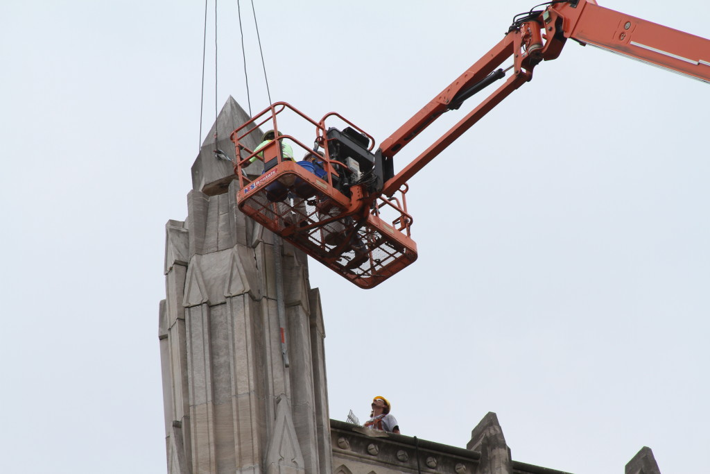 Contractors replace the center stone of Manual's iconic tower