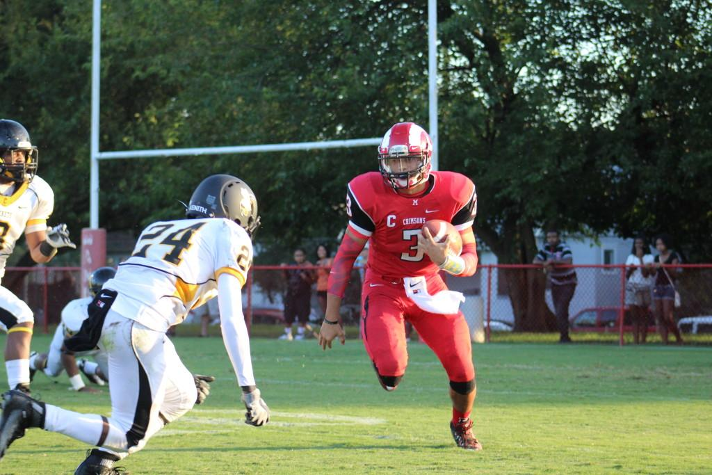 Quarterback Tim Comstock (12, #3) runs for a gain of four at the beginning of the first quarter. Photo by Kate Hatter