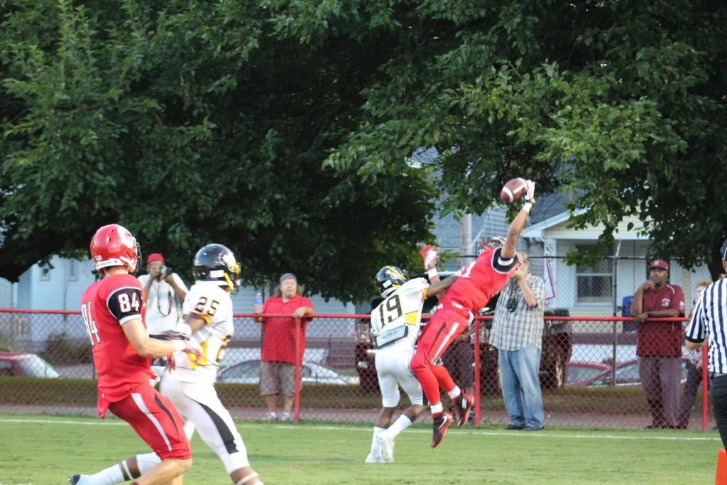 Jailen Carter (11, #11) makes a leaping catch to score Manual's first touchdown of the game. Photo by Kate Hatter