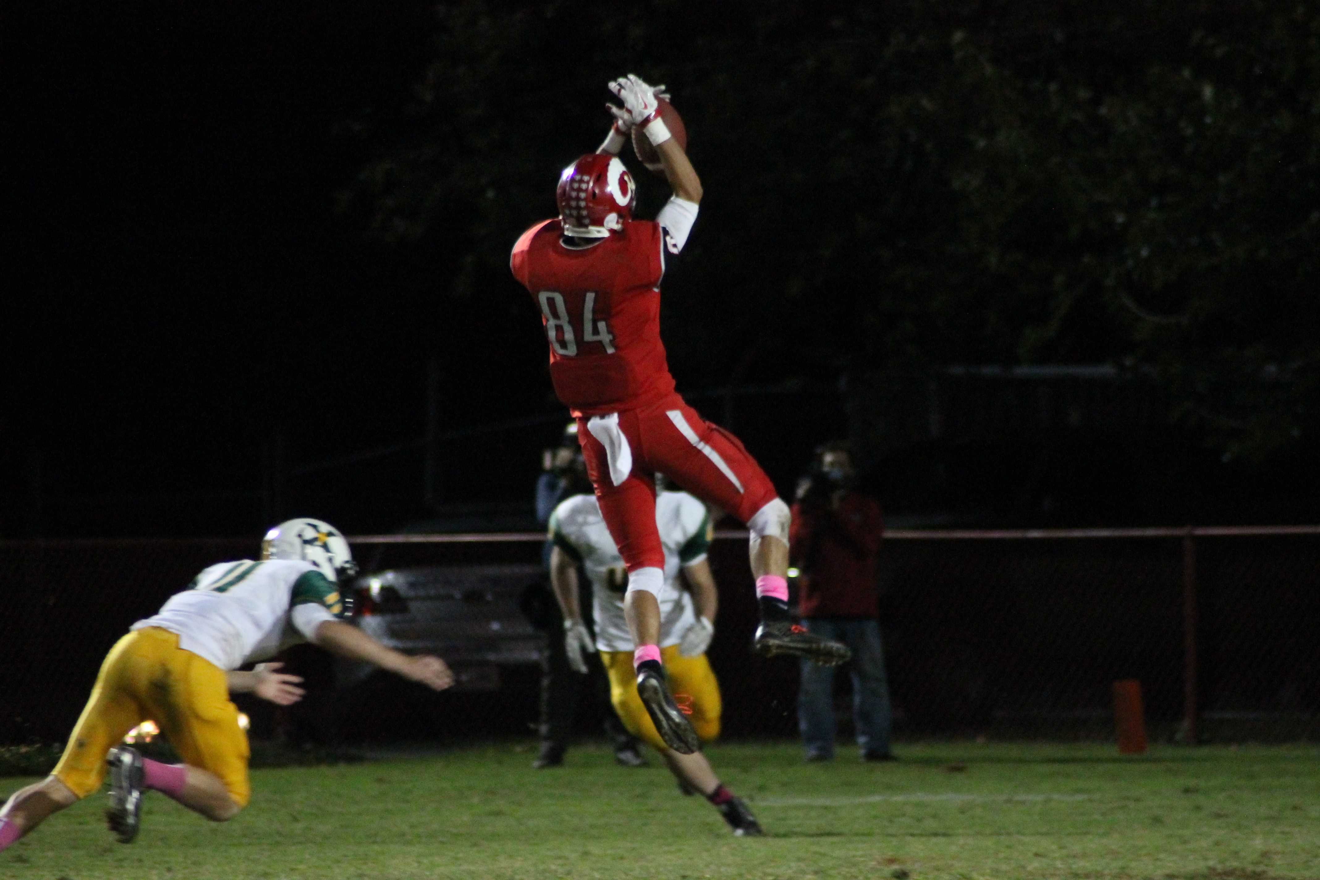 Eric Neimann (12, #84) catches a high pass early in the fourth to give the Crimsons some life. Photo by Roshan Duggineni