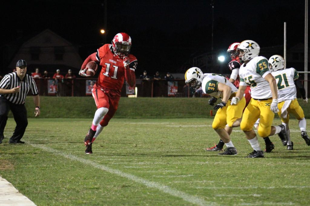 Jaelin Carter (11, #11) skirts past St. Xavier defenders in the first half. Photo by Kate Hatter