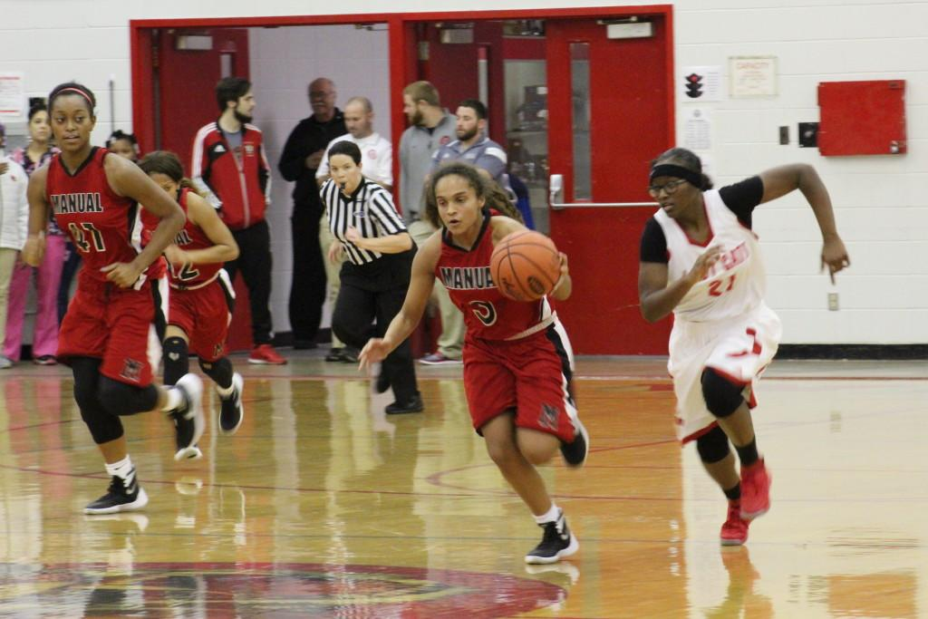 AMy Ballard (9, #3)  leads the Lady Crimsons in transition on one of their many fast breaks. Photo by Kate Hatter.