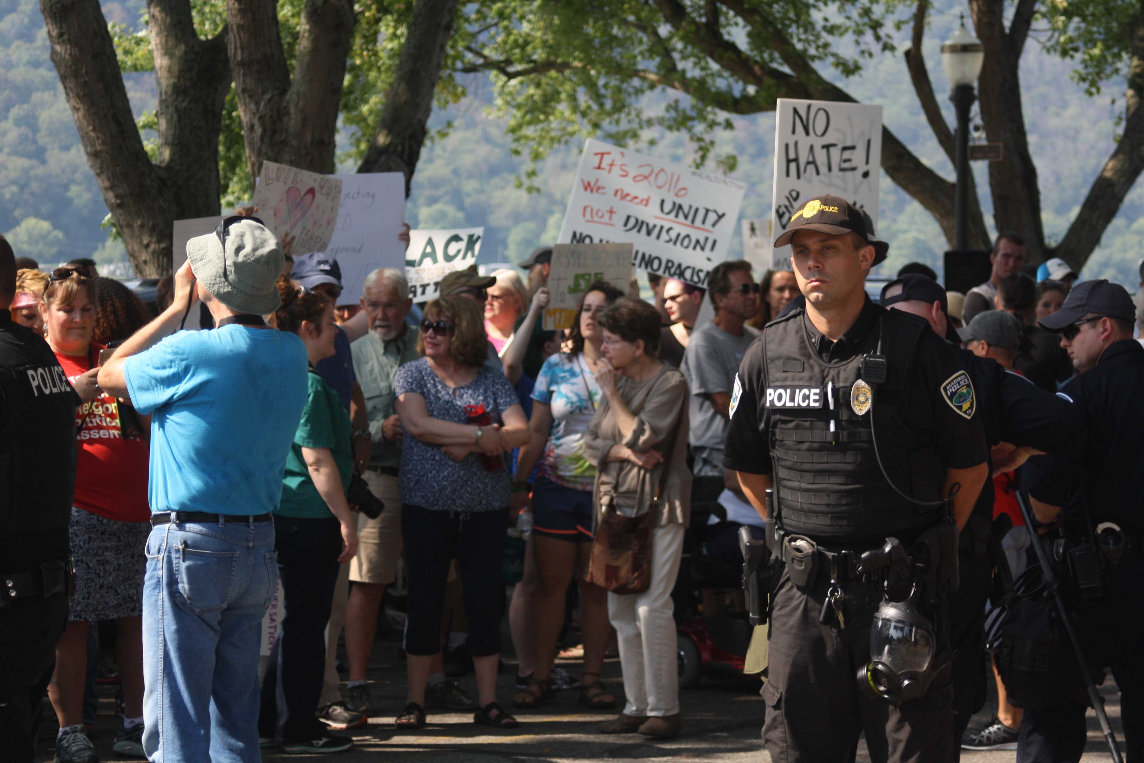 Protesters stand behind police officers. Photo by Phoebe Monsour.