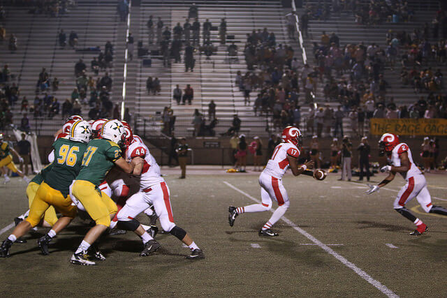 Quarterback W. Britt (17, 12) hands off the ball to M. Floyd (2, 11) - Seyda Muratova