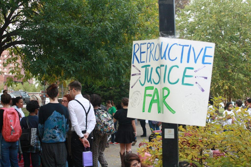 Reproductive Justice Fair sign  hangs on pole. Photo by Phoebe Monsour.