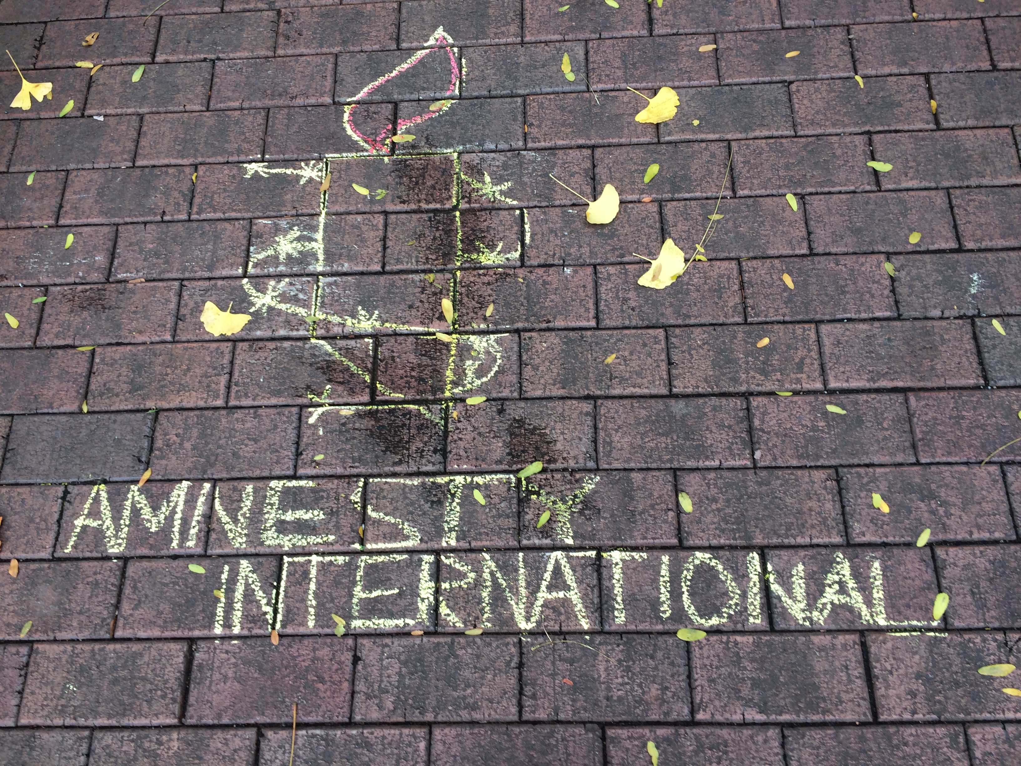 A chalk rendition of Amnesty International's logo, a burning candle, in the Courtyard. Photo by Maya Joshi.
