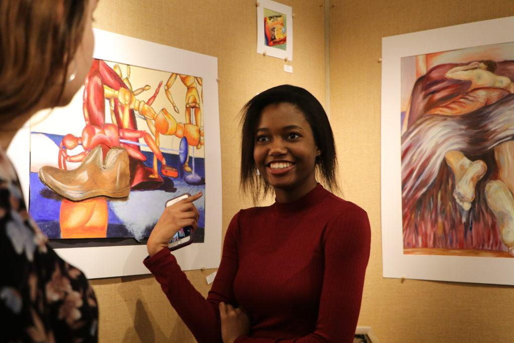 Laurie Jonhatan (12, J&C) cheerfully discusses the artwork with her friend, Olivia Dawson (12, J&C). Photo by Grace Bradley.