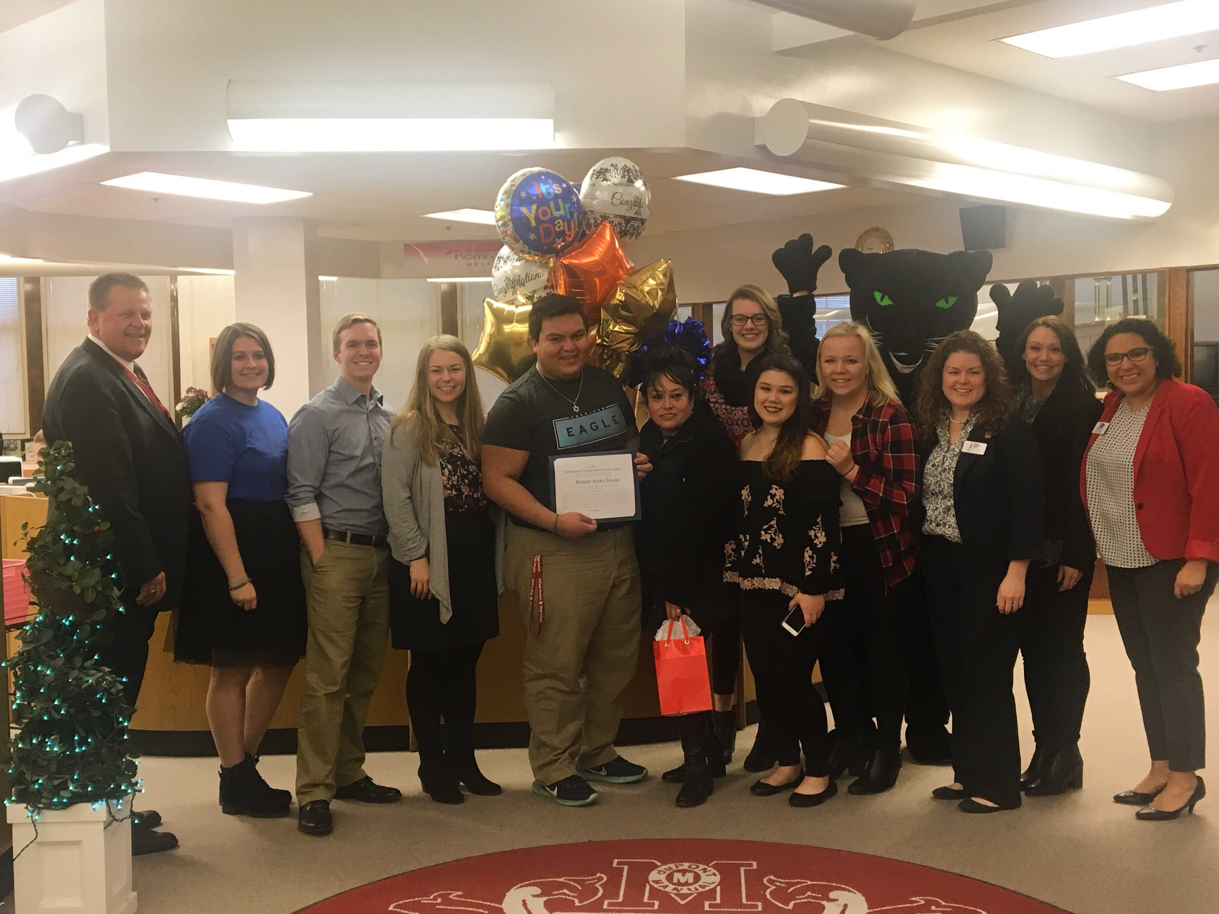 Brayan Aviles (12, HSU) with his mother, friends and representatives form Hanover College after being surprised with a scholarship.
