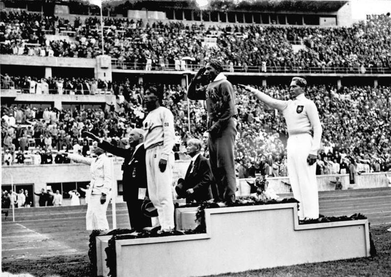 Jesse Owens saluting at the 1938 Berlin Olympics. Photo by the German Federal Archives on Wikimedia Commons. No changes were made to the original image. Image is licensed under Bundesarchiv, Bild 183-G00630 / Unknownwikidata:Q4233718 / CC-BY-SA 3.0. Image link: https://commons.wikimedia.org/wiki/File:Bundesarchiv_Bild_183-G00630,_Sommerolympiade,_Siegerehrung_Weitsprung.jpg