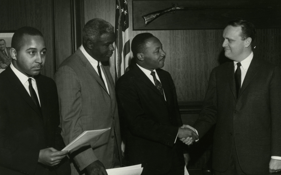 Dr. Martin Luther King, Jr., shaking hands with Kentucky Governor Edward T. Breathitt, Jackie Robinson to King's left, Frank Stanley Jr. to his extreme left, 1964. Photo courtesy of Explore UK.