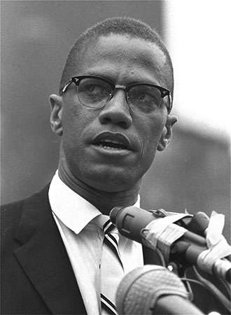 Malcolm X stands giving his famous