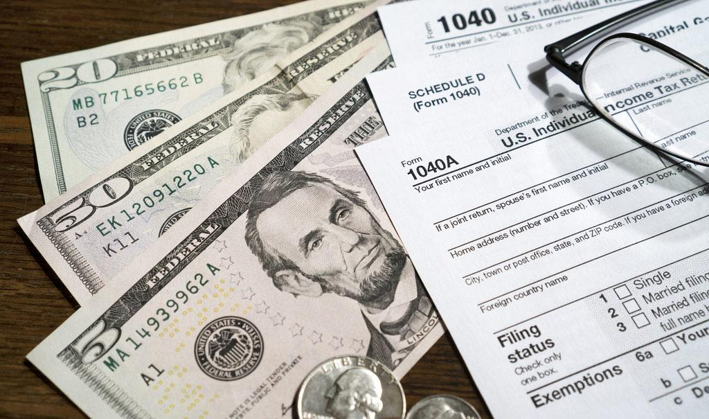 Taxes. Photo by Pictures of Money on Flickr, licensed under CC BY 2.0. No changes were made to the original image. Use of this image does not indicate photographer endorsement of this article. Image link: https://www.flickr.com/photos/pictures-of-money/16687016624
