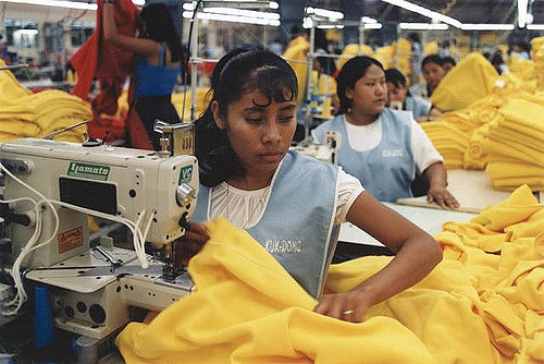 Image of a sweatshop. Photo by Marissa Orton on Flickr, licensed under CC BY-SA 2.0. No changes were made to the original image. Use of this image does not indicate photographer endorsement of this article. Image link: https://www.flickr.com/photos/28876688@N03/2697297072/