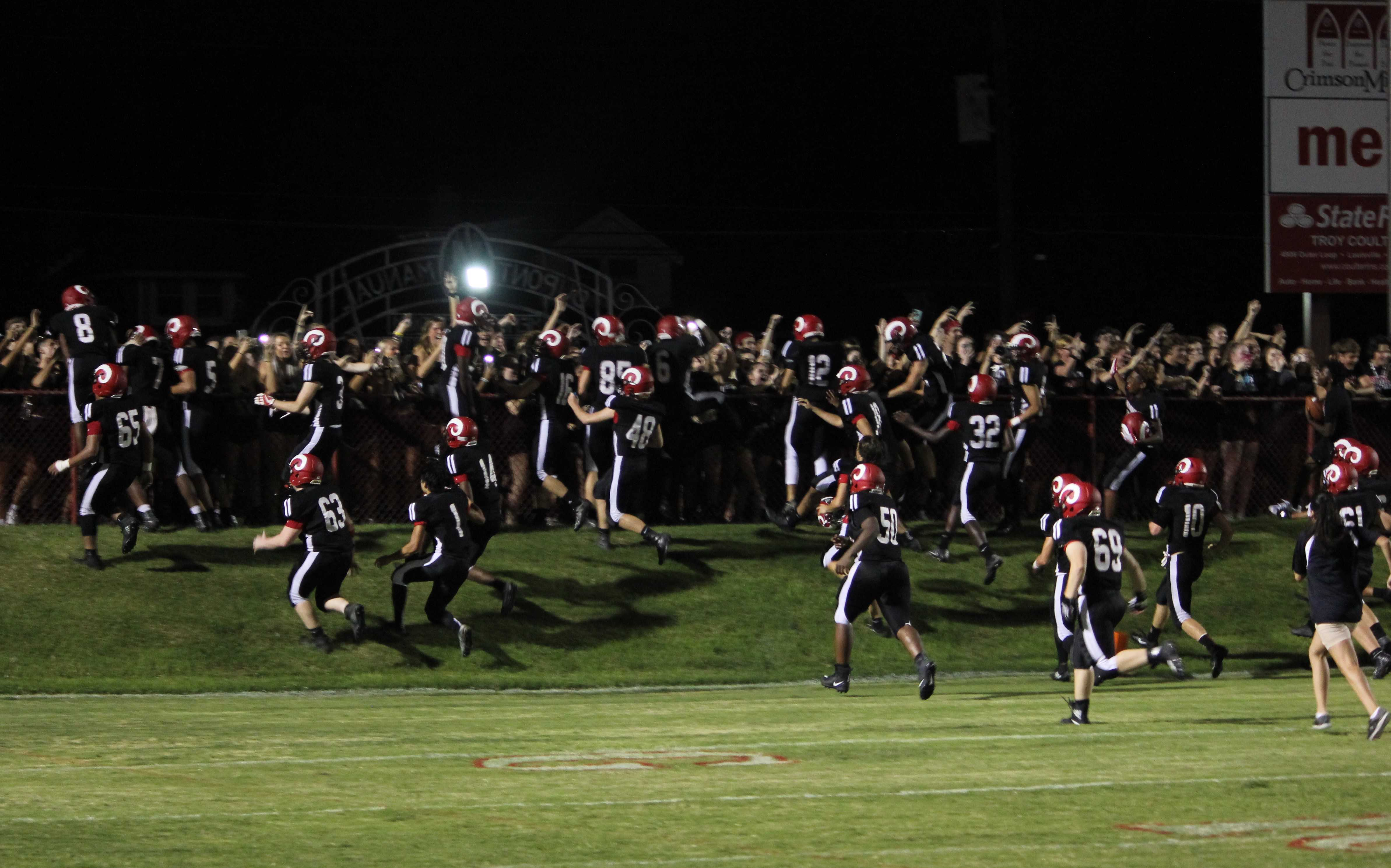 """The Manual football team rushes to meet the fans after their 33-13 win over Fern Creek. """"I'm glad we got to bring the win home to the team,"""" Clayton Awbrey (12, #11) said. Photo by EP Presnell."""