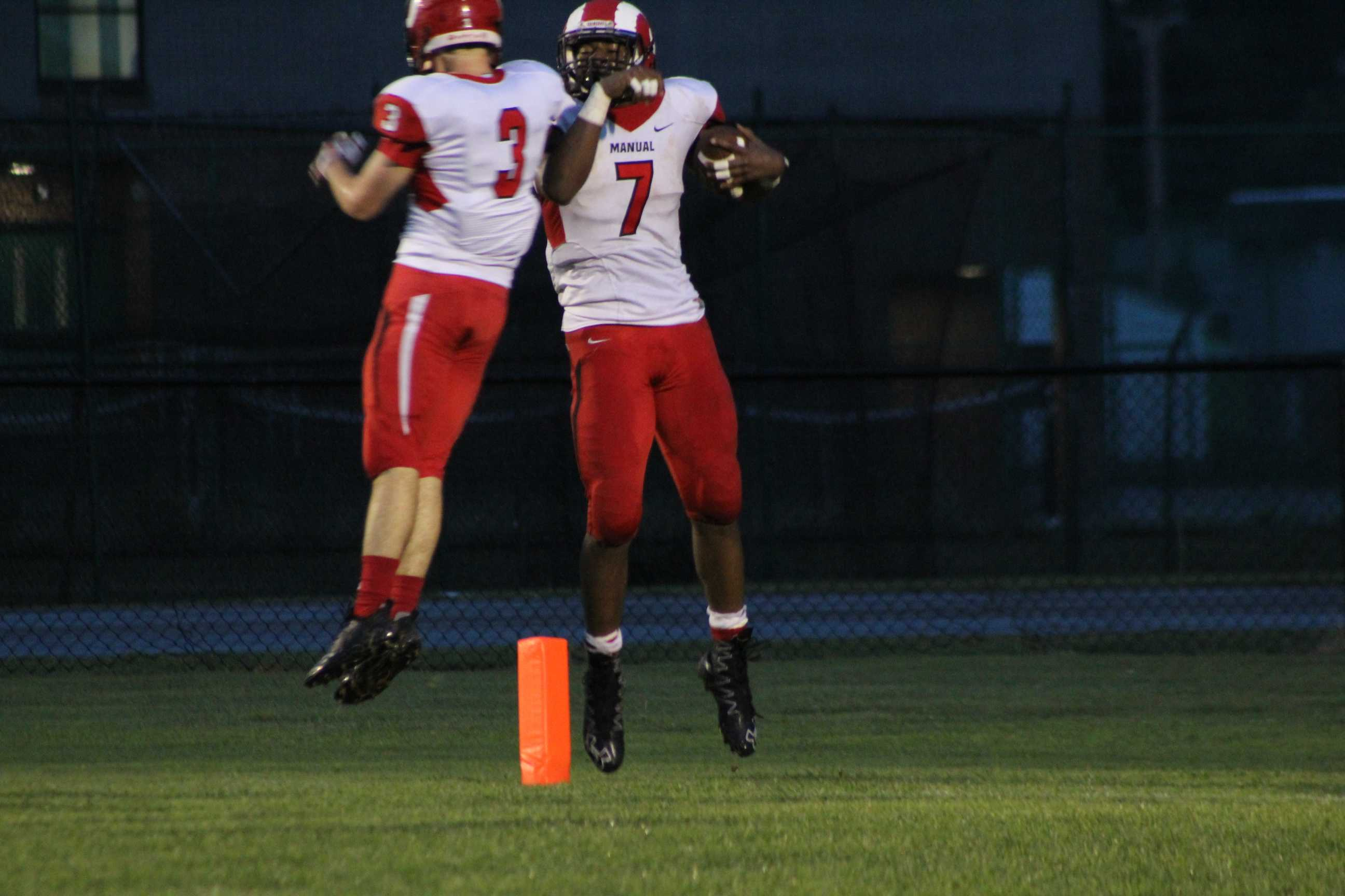 Two Manual football players celebrate after a touchdown. Photo by Maya Joshi.