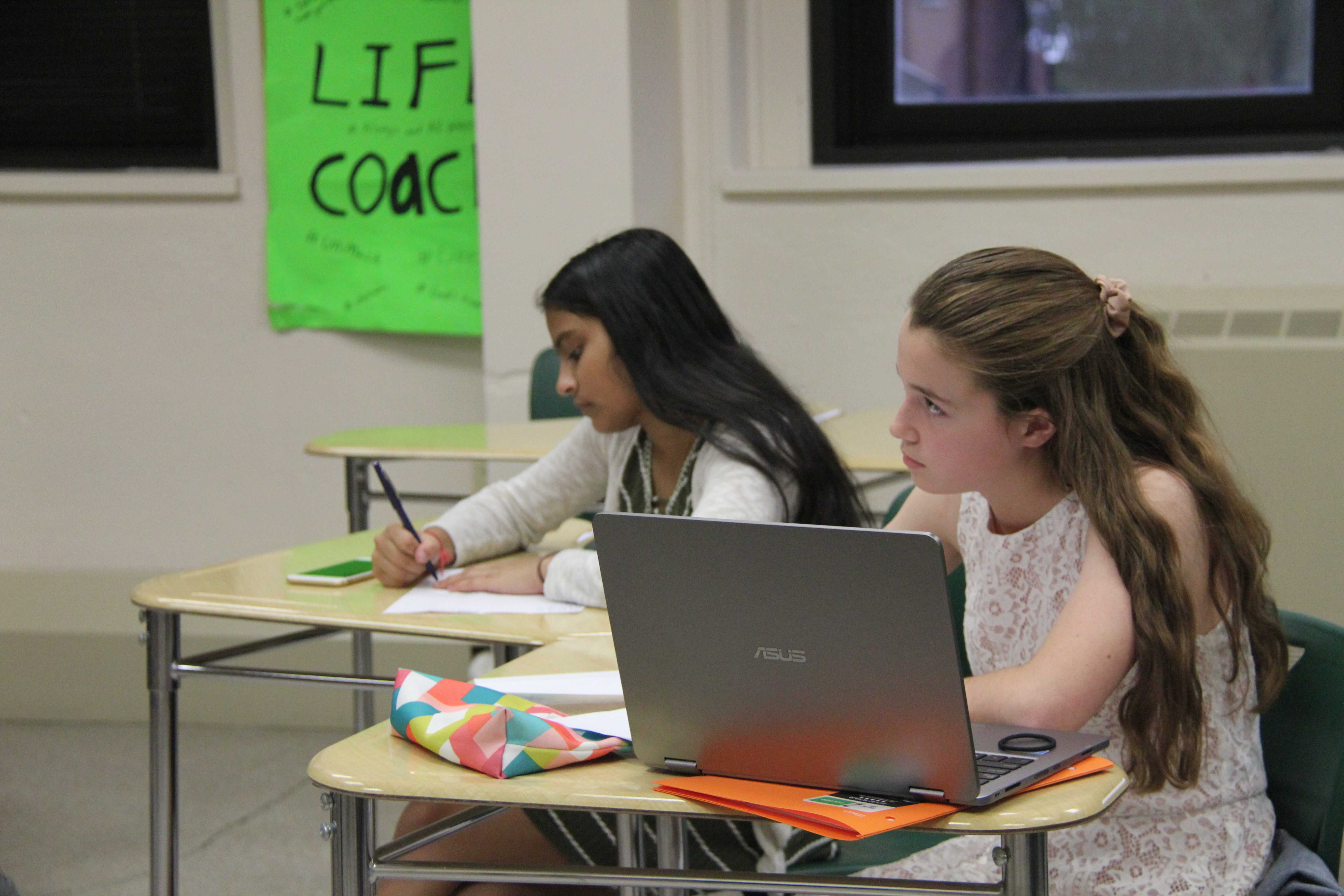 At the Wilson Wyatt Debate League Tournament, two Manual students diligently take notes as their opponent gives a rebuttal. Photo courtesy of Manual Photojournalism Classes.