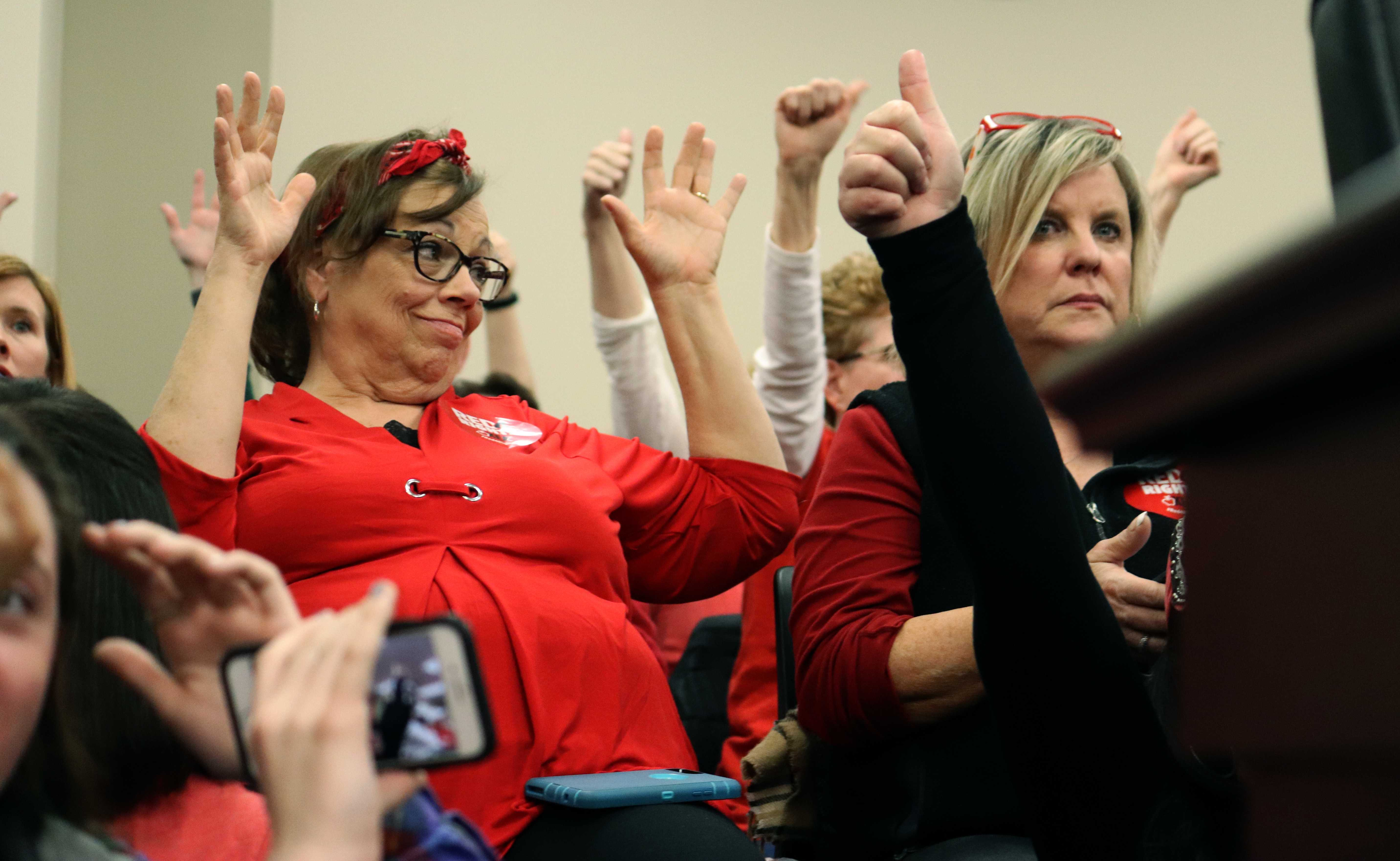 Since the crowd had to stay silent during the meeting, protesters raise their hands to support an opponent of HB 525. Photo by Phoebe Monsour.