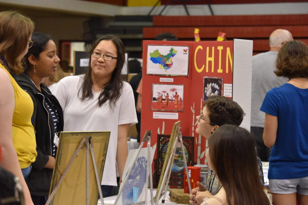 Students gather at the China table to ask questions about current events in the country today. Photo by Piper Hansen.