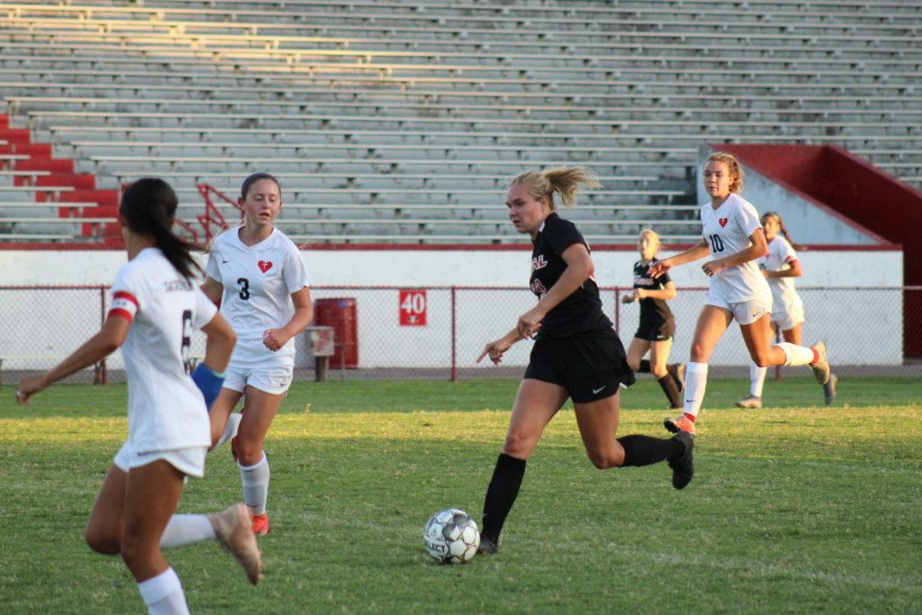 Manual's Savina Zamborini (12, HSU) sprints through past SHA's Anna Buse (#3). Manual lost 1-0. Photo by Molly Gregory.