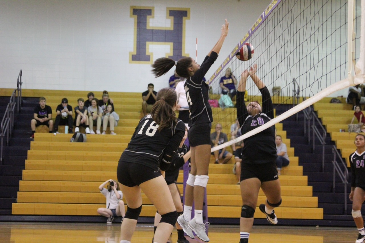 Cecelia Roberts (9, HSU) gets a powerful block out of the middle. Photo by Elizabeth Klein