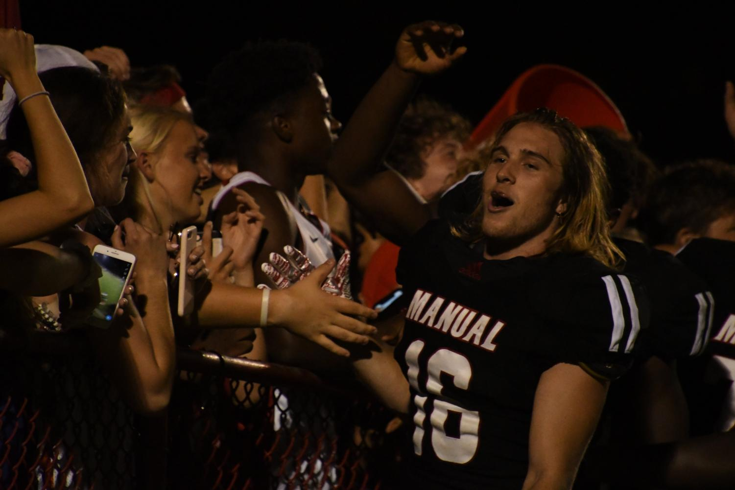 Sean Squires (#16, 12) celebrates at the end zone as the student section and football players sing