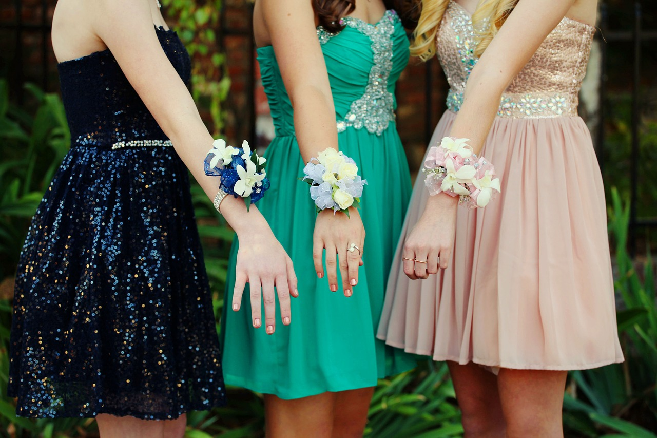 Three girls pose with their corsages before homecoming 2019.